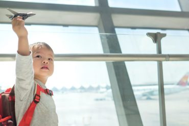 Asian toddler at airport playing with toy plane